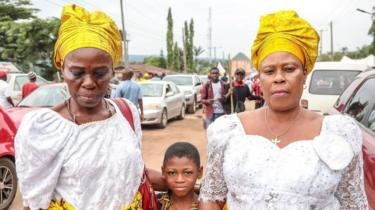 Two women in headwraps with a little boy in a street of Arondizuogu during the Ikeji Festival in Nigeria