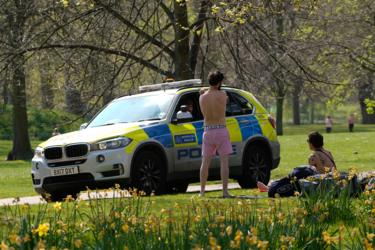 Police officers talk to two men who had been sunbathing in St James's park in central London on Saturday