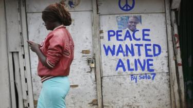 A woman walks past a shop with a message of peace painted recently by local street artist Solomon Muyundo, also known as Solo7, on its door in Kibera slum, one of the opposition leader Raila Odinga