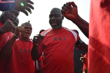 Liberia's president-elect and former football star George Weah (C) reacts with teammates prior to taking part in a friendly football match between Weah All Stars team and Armed Forces of Liberia team