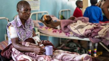 Praise Chipore, 31, sits on a hospital bed at Chimanimani rural district hospital, Zimbabwe, on March 18 2019