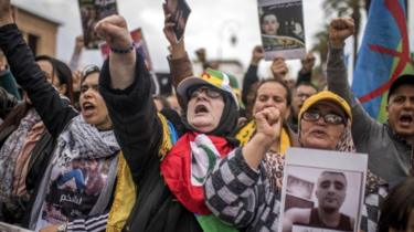 Moroccan protesters hold photos of detainees and shout slogans