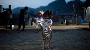 Refugee girl wrapped in a space blanket in Greece