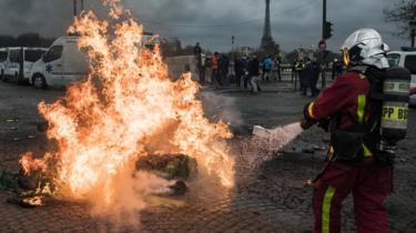 "Firefighters extinguish a fire lit on the street by ambulance drivers on Place de la Concorde during a national ambulance drivers"" protest, in Paris, France, 03 December 2018"