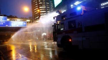 A water cannon is fired at protesters