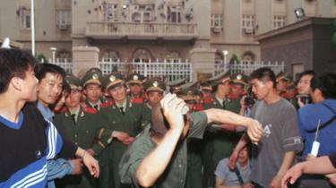 A university student demonstrator throws a rock at the U.S Embassy in Beijing May 9, 1999. Protests have erupted in a dozen or so major Chinese cities, drawing tens of thousands of angry citizens onto the streets. State media has fanned the fury by saying that the NATO bombing of the Chinese Embassy in Belgrade was a deliberate act of aggression.
