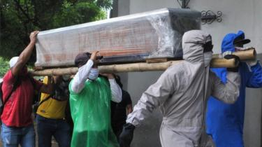 Men carrying a coffin of a suspected Covid-19 victim