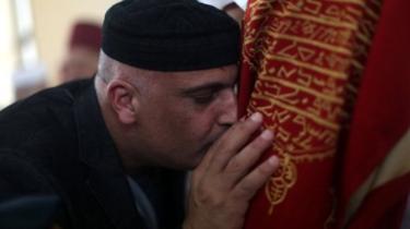 أحد المصلين السامريين وهو يقبل صندوقا يحتوي على لفائف التوراة المقدسة