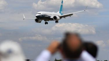Visitors watch as a Boeing 737 Max lands after an air display during the Farnborough Airshow, south west of London, on July 16, 2018.
