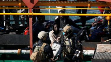 Maltese special forces soldiers guard a group of migrants on the merchant ship Elhiblu 1 after it arrived in Senglea, in Valletta's Grand Harbour, Malta, on 28 March 2019