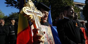 A Romanian Orthodox nun holds a cross, a national flag and an icon during a support rally for the family re-definition referendum planned for this weekend, in the small city of Draganesti Olt, 260 kilometers south-east from Bucharest, Romania, 04 October 2018.