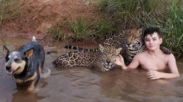 Tiago com duas onças no rio