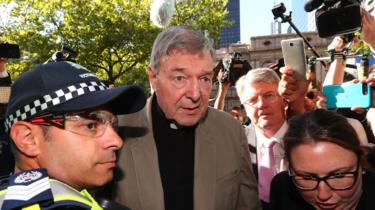 George Pell is escorted by police through a crowd of media and onlookers outside a Melbourne court at the start of his sentence hearing.