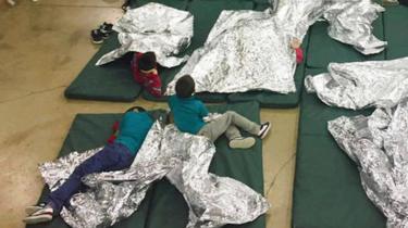 Três meninos sobre colchões verdes, próximos a cobertores de alumínio em centro de detenção para imigrantes
