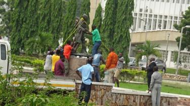 Men removing the Gandhi statue