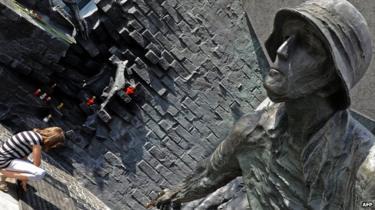 Mulher num monumento de Varsóvia em comemoração dos polacos que combateram as tropas de ocupação alemãs durante a Revolta de Varsóvia no Mundo Guerra II