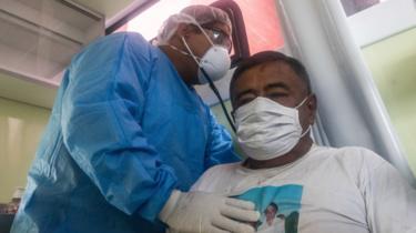 Seorang dokter yang mengenakan APD merawat pasien Covid-19 di Peru.