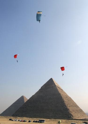 Three powered paragliders take part in the air games festival in front of the Giza pyramid complex, in Giza, Egypt - Monday 19 February 2019