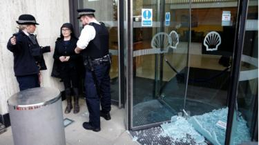 Police officers talk to a climate change activist outside Shell's London HQ