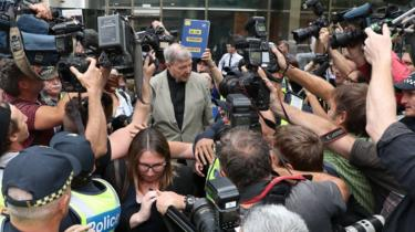 Pell is surrounded by media as he left court on Tuesday after a reporting ban on his conviction was lifted
