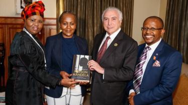 """Temer segura o livro """"The prison letters of Nelson Mandela"""" (As cartas da prisão de Nelson Mandela, em tradução literal), em foto com a ministra de desenvolvimento de pequenos negócios, Lindiwe Zulu (à esquerda), com Ndileka Mandela, Neta de Mandela, e com o CEO da Fundação Mandela, Sello Hatang, tirada em Joanesburgo"""