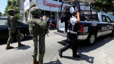 Mexican Marines escort municipal police officers disarmed and detained on suspicion they colluded with organised crime, in Acapulco. Sept 2018