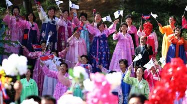 North Koreans in traditional attire wave flags to welcome Moon Jae-in to Pyongyang