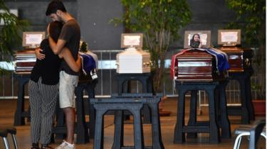 Mourners hold each other by the coffin of a victim of the Morandi bridge collapse in Genoa, on August 17, 2018.