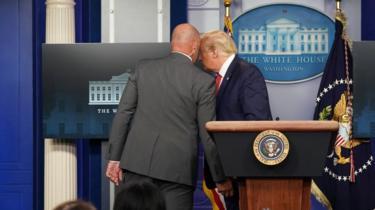 O presidente dos Estados Unidos, Donald Trump, conversa com um agente do serviço secreto antes de deixar uma reunião sobre o coronavírus na Casa Branca, em 10 de agosto de 2020