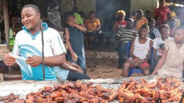 Man selling chicken in a street of Arondizuogu during the Ikeji Festival in Nigeria