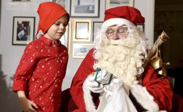 A man dressed as Santa Claus visits a family on Christmas Eve in Espoo