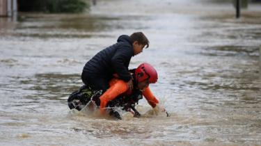 A French firefighter carries a child during rescue operations in the middle of submerged streets due to heavy rain falls and violent storm that hit Aude on 15 October 2018.