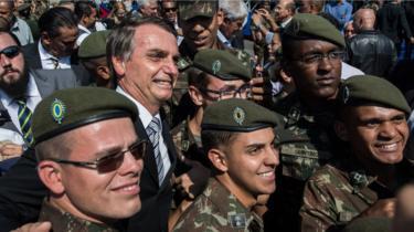 Jair Bolsonaro poses with members of the military