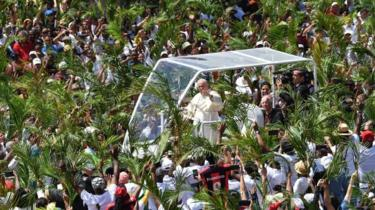 Pope Francis waves as he arrives prior to leading a mass in Mauritius