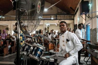 A drummer dressed in a white suit performs during service at St Mary's Catholic church in Port Harcourt, Nigeria - Sunday 17 February 2019