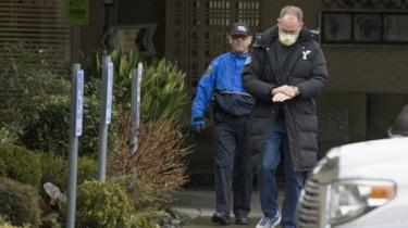 Two men emerge from a nursing home, one in official uniform and the other washing his hands, that reported several cases of coronavirus in Washington State.