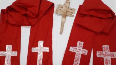 Red robes with homemade crosses on them