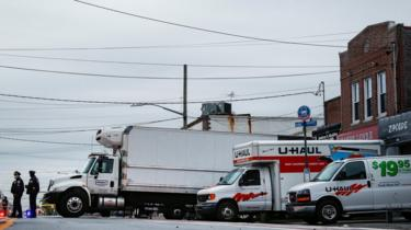 Police stand by trucks filled with dead bodies in New York