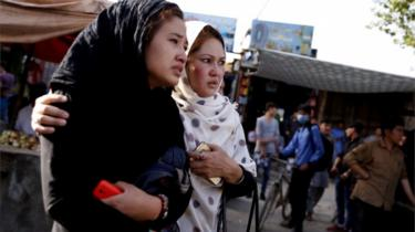 Two women look on to the blast scene