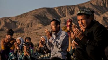 A Uyghur family pray at the grave of a loved one - 2016