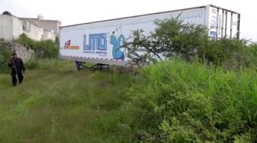A police officer walks alongside an abandoned trailer full of bodies in Tlajomulco de Zuniga, Jalisco, 15 September 2018