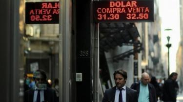 "People walk past an electronic board showing currency exchange rates in Buenos Aires"" financial district, Argentina August 29, 2018"