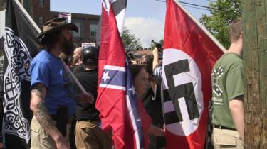 Demonstrators carry confederate and Nazi flags during the Unite the Right free speech rally at Emancipation Park in Charlottesville, Virginia, on August 12, 2017