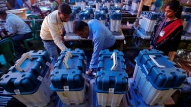 officials check voting machines