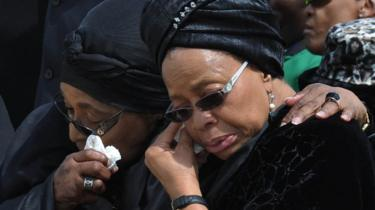 ex-wife of Nelson Mandela, Winnie Mandela Madikizela (L), and his widow Graca Machel wipe their tears upon their arrival with the remains of South African former president Nelson Mandela at the airport in Mthatha on December 14, 2013.
