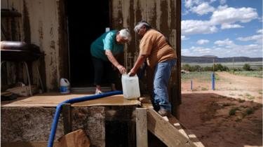 Navajo people collecting water