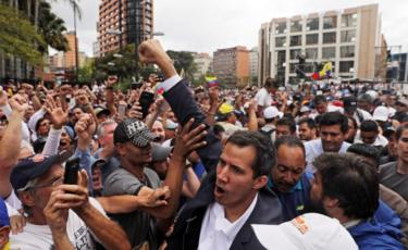 Juan Guaido, President of the Venezuelan Parliament, greets a crowd in Caracas after announcing he was assuming executive powers on 23 January 2019