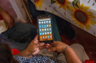 Maria del Rosario Rodriguez, holds her son's Ricardo Flores' cell phone, in their family's home in Acatlán, Puebla, Mexico, October 18, 2018