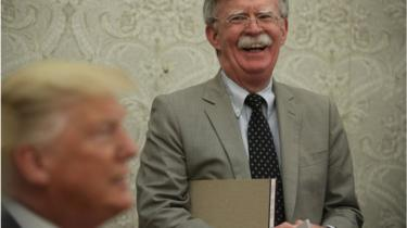 President Donald Trump speaks to members of the media as National Security Adviser John Bolton listens during a meeting with President of Romania Klaus Iohannis in the Oval Office of the White House August 20, 2019