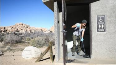 A volunteer cleans a restroom at Joshua Tree National Park